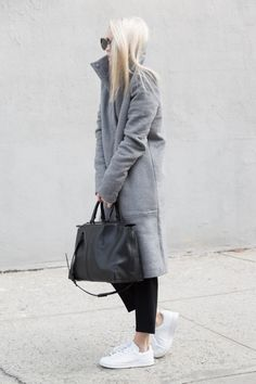 Figtny is wearing a grey funnel neck coat from Oak + Fort, black trousers from Aritzia and white Adidas