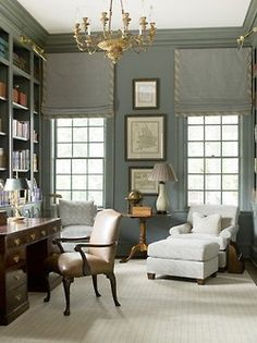 Deliciously grey study by Phoebe Howard. Love the pops of gold provided by the chandelier and the library lights, and the ticking tape trim on the roman shades.