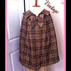 "✨Vintage Wool Plaid Custom Made Bow Neck Cape✨ An incredible find that unfortunately is too big for me. Vintage wood tweed plaid cape with large bow at collar. The plaid has brown, tan, gold colors with hints of pink throughout. Two snaps at collar and two arm slits. Gentle large pleats all around starting at shoulders. Lined in vibrant gold satin. Believe this to be custom made- tag reads 'Custom Original Tailoring for Alice E Smith'. Thanks Alice! Measures 20"" across shoulders, 34""…"