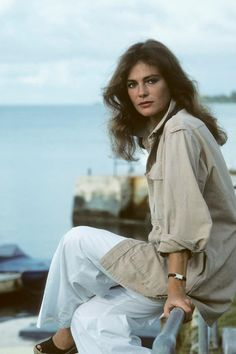 1970s Fashion Icons - Actress Jacqueline Bisset with dreamy brushed out 70s curls, wearing a khaki cargo jacket and white trousers