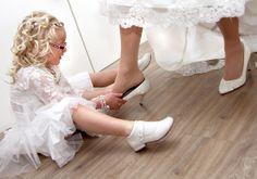 Dochterje van de bruid helpt met de schoenen aantrekken.  Ook een mooie bruidsreportage? www.hanenhanneke
