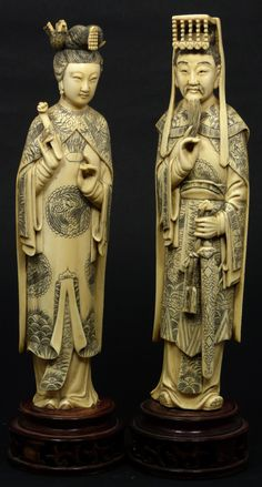 """Pair of Chinese ivory hand carved figures depicting Emperor & Empress. The emperor holding ceremonial sword with hand to beard. The Empress is depicted holding ruyi scepter with pheonix head dress. Each figure is wearing layered robe with intricate water and fire design with lotus blossoms. Both mounted to round wooden bases. 19th/20th century. Each measures approximately 10"""" height + 1 5/8"""" height (25.4cm + 4.1cm). Total weight approx. 1057 grams."""