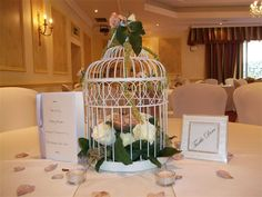 Birdcage centrepiece filled with vintage roses with scattered rose petals