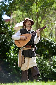 A traveling minstrel/troubadour. Playing a string guitar entertaining his audience with music. Notice his troubadour pants and his longer not quite so fitting blouse. You would also see the hats with a feather out the back.