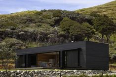 A dark rough-sawn timber box in New Zealand, Storm House.