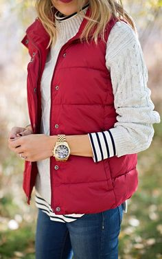 A red vest for fall paired with gold accessories is a casual yet updated choice.I love the red vest and sweater but do not need jewelry. I would love a vest in white too Red Puffer Vest, Red Vest, Puffer Vest Outfit, Vest Jacket, Burgundy Vest, Navy Vest Outfit, Sweater And Jeans Outfit, Puffy Jacket, Black Vest