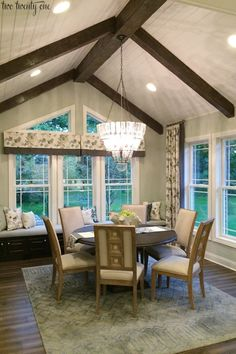 dining room with wooden ceiling beams and window seat