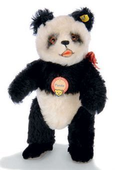 A STEIFF FIRST-TYPE JOINTED PANDA, (5330,2), black and white mohair, brown and black glass eyes, black stitching, small open mouth, gray leatherette pads, inoperative squeaker, ribbon, script button, yellow cloth tag and chest tag, 1949 --11¾in. (30cm.) high