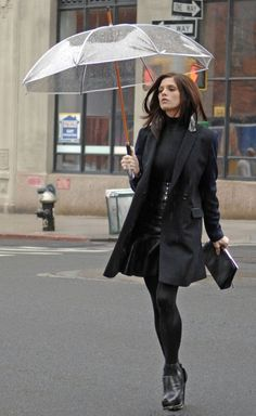 Ashley Greene wearing a black full hands top and black skirt and posing with an umbrella.