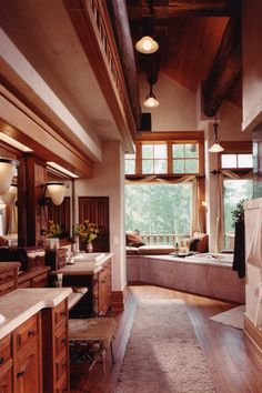 Sprawling bathroom beneath a vaulted ceiling spreads an array of natural wood, from hardwood flooring to vanity cabinetry, in an elaborately shaped space. Corner soaking tub is framed in marble tile beneath a set of immense windows overlooking a balcony and forest beyond.