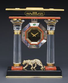 "CARTIER ""THE EGYPTIAN TEMPLE PANTHER PORTICO MYSTERY CLOCK"" AN IMPORTANT AND VERY RARE YELLOW GOLD, DIAMOND, EMERALD, BLACK MOTHER-OF-PEARL, ROCK CRYSTAL, PINK CORAL, BLACK ENAMEL, BLACK AGATE, SMOKEY QUARTZ, TWO COLUMN MYSTERY CLOCK, IN EGYPTIAN STYLE CIRCA 1990 CASE 620913"
