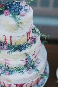 Naked Wedding Cake - Featured is a three-tiered Vanilla Bean Naked Wedding Cake with Vanilla Bean Buttercream, a raspberry/blueberry filling and a light dusting of powdered sugar. Topping this cake are fresh blueberries and raspberries, thyme and lavender. Not pictured are two mini naked cakes!