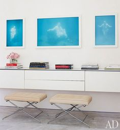 A series of bright artworks hang above a minimal vanity in the master bedroom of…