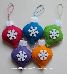 A handmade set of 5 brightly coloured felt snowflake Christmas ornament/decorations. Each ornament is made from wool blend felt and glitter fabric. A plastic snowflake button is added for texture and detail. Each decoration is filled with polyester stuffing that meets British and