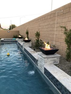 Firebowls are the latest go to in swimming pool design. 80's and 90's it was the rock waterfalls and slides. Today families are seeking the water and fire atmosephere in their backyard oasis. It brings the feel of luxury camping or resort right to your own backyard. Swimming Pool Designs, Swimming Pools, Pool Finishes, Rock Waterfall, Fire Bowls, Luxury Camping, Oasis, Backyard, Waterfalls