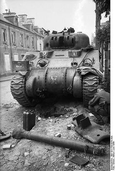 Sherman tank has met its demise in the streets of Villers-Bocage, France, June 1944. This must have been an extraordinary shot by the Germans: the Sherman's gun barrel along with the base armored shield have been blown clear off the turret; the shield can be seen on the sidewalk next to what looks like a broken wooden pole
