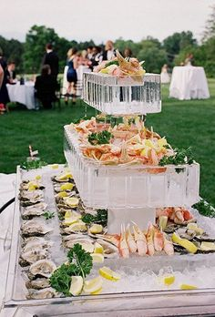ice sculpture raw bar featuring tiers of fresh crab legs and oysters / http://www.deerpearlflowers.com/wedding-food-bar-ideas/2/