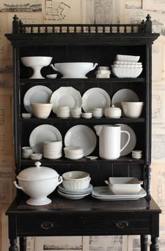 Pretty black cabinet with white dishes.