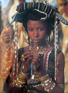 "Africa | ""During the dry season, as they travel from camp to camp on donkeys, the young Wodaabe girls embroider blouses and skirts and collect some objects from which to make jewellery in prepartion for the 'Geerewol' cermony.  This festival provides the main chance of the year for them to initiate relationships and to find a 2nd, 3rd or 4th husband"" 