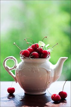 Teapot full with cherries