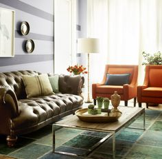 Love the mismatched living room seating and the orange chairs with multicolored rug!