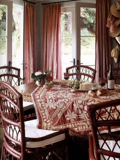 Dining room: red wicker chairs with white seat cushions, red and white embroidered table cloth -- Mary McDonald