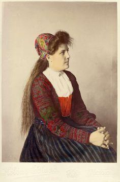 Foto, taget snett framifrån, på en ung kvinna i dräkt från Delsbo, Hälsingland i stickad tröja och kattunmössa s.k. påsluva