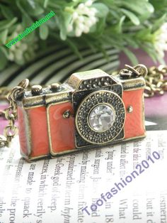 Pretty retro copper white crystal 3d camera with orange glaze necklace pendant jewelry vintage style. $4.99, via Etsy.