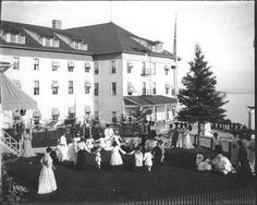 Children's party on the lawn of the Newberry Cottage, with west wall of Grand Hotel in the background by William H. Gardiner.