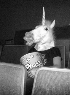 Unicorns eating popcorn in movie theatre, watching movies tv,  black white photography human in unicorn head, mask costumes,