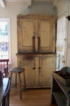 FARMHOUSE – INTERIOR – an antique cupboard is at the center of this farmhouse kitchen.
