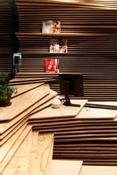 把木板分層堆疊成『丘陵』地形結構,並以此延伸出櫃檯與四周的座位區,以及用於展示各種出版品的地方。
