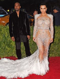 The Most Jaw-Dropping Dresses at the 2015 Met Gala | KAYNE AND KIM KARDASHIAN WEST | Kayne in a white jacket and pants with fringed scarf, and Kim in a wearing a see-through, heavily embellished beaded gown with fringe train (the first from Peter Dundas's return to Roberto Cavalli).