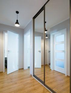 """Tmavou chodbu """"prosvětlila"""" bílá výmalba, zrcadla a prosklené dveře."""