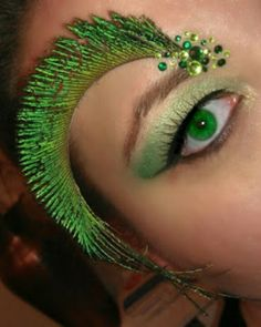 Peacock inspired eye make-up complete with feather brow and green crystal accents.
