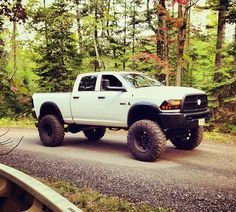 white lifted Dodge Cummins diesel truck with huge tires Ram