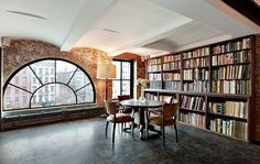 Ahhh a window with a view of New York is always fabulous but this is super lovely with the brick and the books...