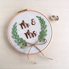 Whether you are needing a gift for the new bride and groom, redecorating your home or celebrating an anniversary. Not only will they add a personal touch to your home, with a little ribbon, you can turn the embellished hoop into a ring holder.  After the wedding this hoop can either be hung on a wall or placed on a shelf as a keepsake from the couples special day.  Details: + This hoop is hand-embroidered on 100% cotton fabric with 100% cotton thread. + The fabric is set in a 6 (aprox. 16…