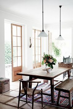 rustic dining room with exposed wooden bench seat, pendant lights with white glass shades, terracotta tiles
