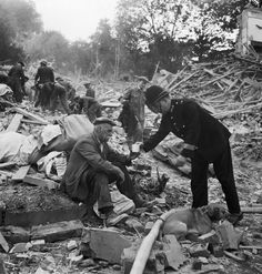 Devastation caused by a flying bomb, London 1944: PC Frederick Godwin of Gipsy Hill Police Station supplies tea and sympathy to a now homeless man after a V1 attack that sadly killed his wife and destroyed his home. He returned from taking his dog (also pictured) for a walk to find a scene of devastation. In the background, rescue workers can be seen searching the rubble and debris for any survivors of this attack which destroyed almost an entire street.    Imperial War Museum