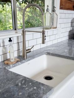 Quartzite countertops, an undermount sink and a contemporary faucet bring a utilitarian yet modern aesthetic to this kitchen featured on HGTV's Fixer Upper.