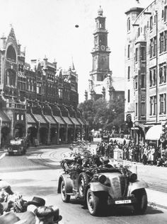 """Raadhuisstraat, Amsterdam, The Netherlands, 16 May 1940. The German Wehrmacht arriving in Amsterdam. """"Thousands of citizens of Amsterdam lined the roads to watch the impressive panzer vehicles, motorcycle brigades, army vehicles and so forth, that filed past in perfectly disciplined columns."""""""
