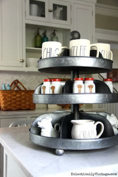Industrial tiered tray in the kitchen - perfect for showing off favorite things in the like the vintage spice jars and these mugs with fun words engraved on them from HomeGoods eclecticallyvintage.com sponsored pin