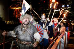 vikings invade darling harbour - Group of people dressed as Vikings walk up ramp, holding fire torches