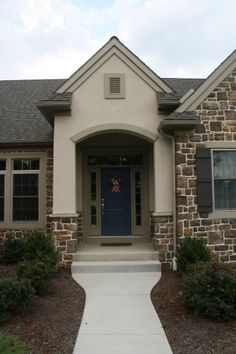 Custom home with stone veneer, board and batten shutters, and a blue front door with sidelights and a transom.