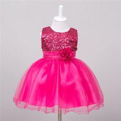 Feestelijk roze jurkje met pailletjes op het bovenstuk, bloemversiering op het voorpand en aanknooplint op het achterpand. Het rokje bestaat uit twee lagen organza, een polyester onderlaag en daaronder een binnenrokje. Kuitlengte.     Model: Louise Baby
