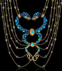 Boucheron - The necklace features two intertwined snakes which are inlaid with emeralds, sapphires, turquoise scales with matte gold.