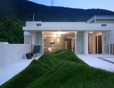Undulating lawn is on the terrace of a penthouse called Axial Symphony in Shenzhen, China. Designed by Hong Kong Studio Design Systems, the home was built along several axis in order to make the residents feel like they are at the center of their home as they move around the property.