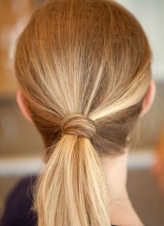 After you've tied your ponytail, grab a section about the width of your pinky from the pony and wrap it around the base. Tuck in any loose ends and secure it by inserting a bobby pin.