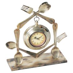 Metal table clock with a fork and spoon design. Product: Table clockConstruction Material: Metal and glassColor: SilverFeatures: Utensil designAccommodates: AA Battery - not includedDimensions: H x W x D